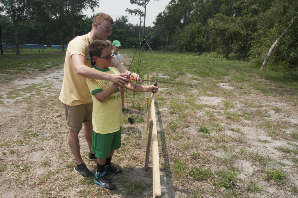 Camp counselor helping camper practice archery.