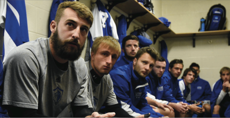 Above: Anderson (left) with his teammates in the locker room listening to an inspirational speech from their coach before a big game. LU Photos.