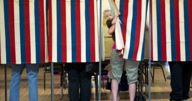 Landon Peterson peeks out of the voting booth while his mother Meghan votes March 20, 2012 at Christian union Church in Metamora, Illinois. White House hopeful Mitt Romney eyed a big win in President Barack Obama's home state Tuesday as he sought to clinch the Republican nomination and focus on November's general election. Polls across Illinois opened for the state primary at 6:00 am (1100 GMT) with former Massachusetts governor Romney the odds-on favorite to win.   AFP PHOTO/DON EMMERT (Photo credit should read DON EMMERT/AFP/Getty Images)