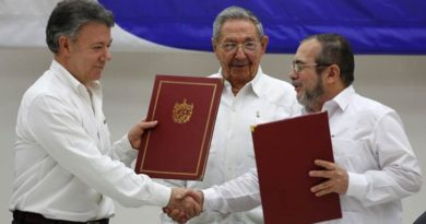 Colombian President Juan Manuel Santos, left, and Commander of the Revolutionary Armed Forces of Colombia or FARC, Timoleon Jimenez, right, shake hands during a signing ceremony of a cease-fire and rebel disarmament deal, in Havana, Cuba, Thursday, June 23, 2016.  The deal moves Colombia closer to ending a 52-year war that has left more than 220,000 people dead. Pictured in the center is Cuba's President Raul Castro. (AP Photo/Desmond Boylan)