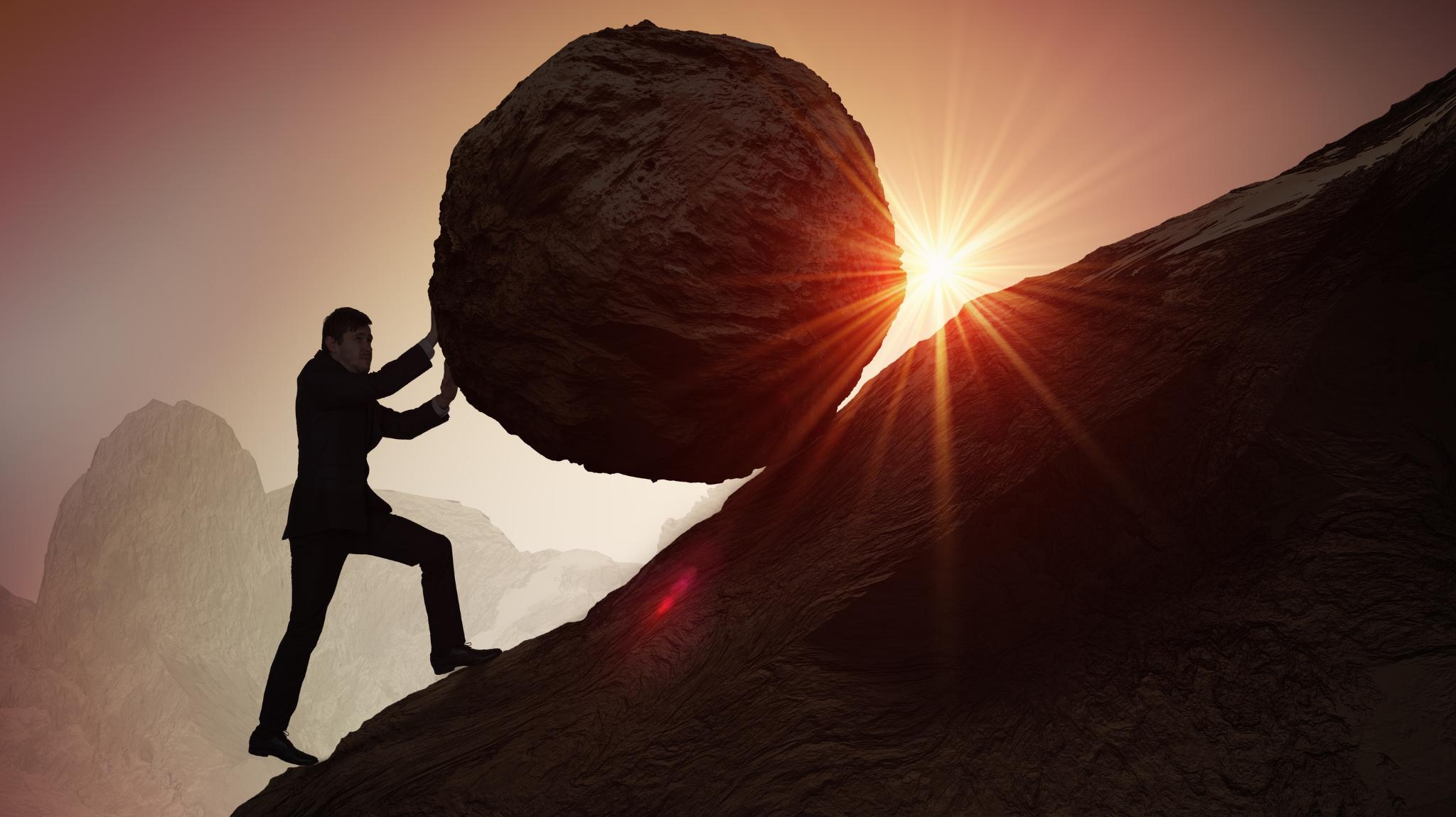 Man pushing boulder up a mountain