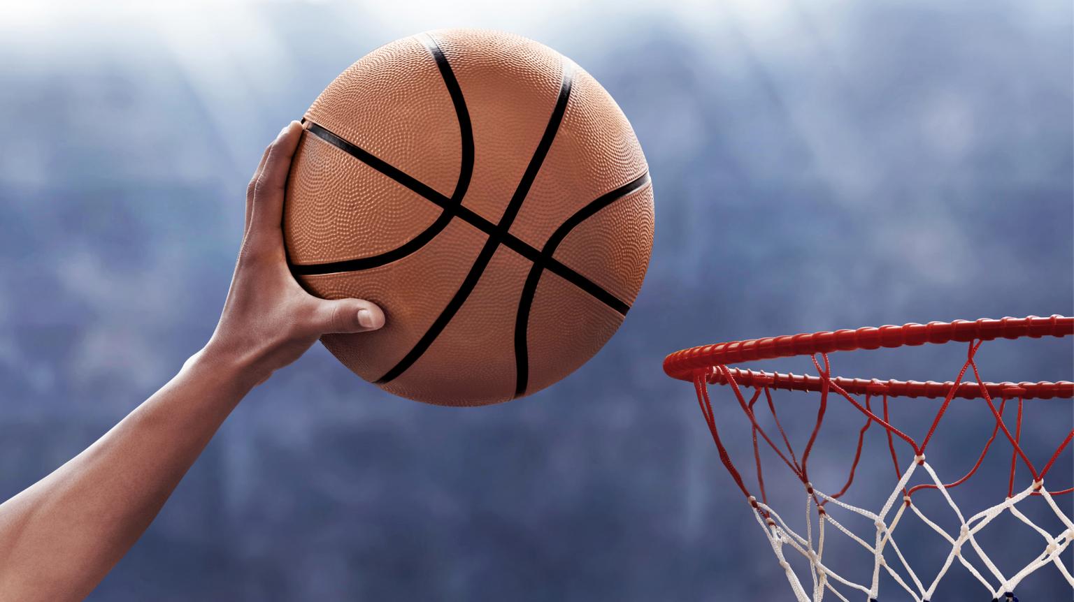 Hand dunking basketball